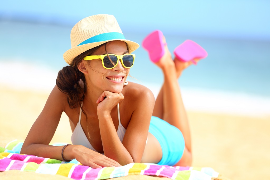 Beach woman funky happy and colorful wearing sunglasses and beac